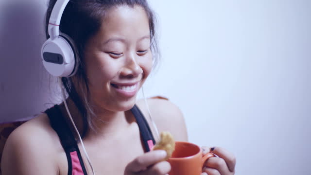 Escuchar música joven asiática y pausa para tomar café. - vídeo