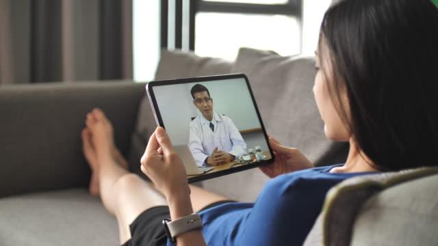asiatisk ung kvinna som ligger på en soffa och video konferens med läkare på tablet pc hemma - videor med medicinsk undersökning bildbanksvideor och videomaterial från bakom kulisserna