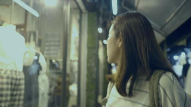 asiatisk ung kvinna shopping på modemarknaden - spendera pengar bildbanksvideor och videomaterial från bakom kulisserna