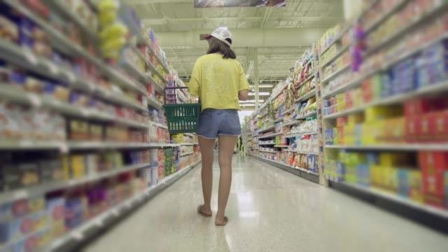 vídeos y material grabado en eventos de stock de joven asiática de compras en supermercado - snack aisle