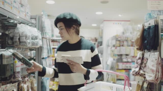 vídeos y material grabado en eventos de stock de asiática chica de compras en el supermercado - snack aisle