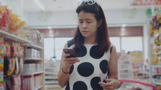 vídeos y material grabado en eventos de stock de mujer joven asiática comprando en supermercado - snack aisle