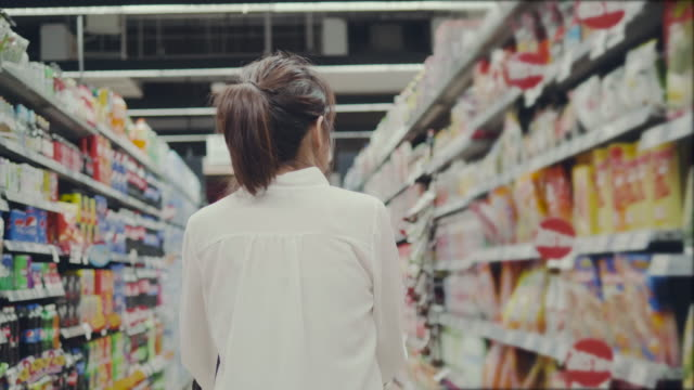 Asian young woman shopping in supermarket Asian businesswomen buying food in supermarket. snack stock videos & royalty-free footage