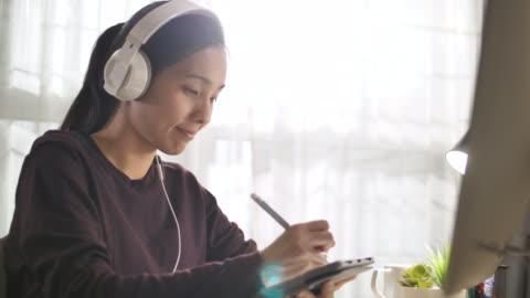 giovane donna asiatica che studia online a casa - imparare video stock e b–roll