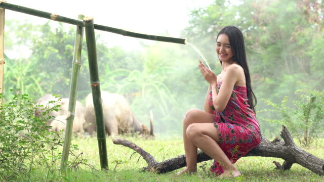 Asian young woman take a shower outdoor with buffalo in the morning, local background, nature traditional country of Thailand.