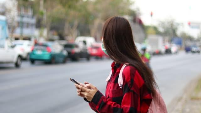 asiatische junge frau mit smartphone in der stadt - smartphone mit corona app stock-videos und b-roll-filmmaterial