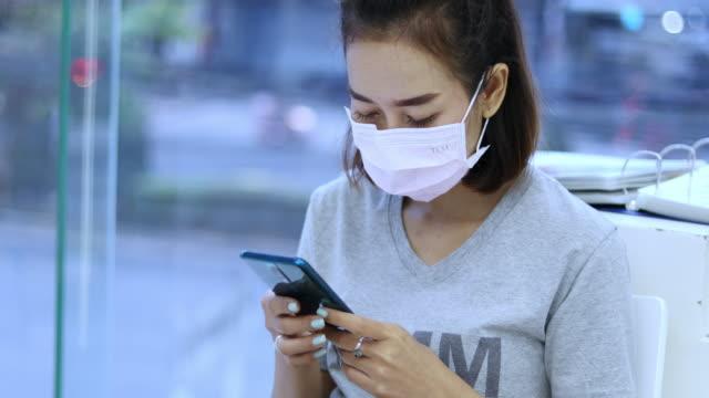 asiatische junge frau mit smartphone in der stadt trägt gesichtsmaske wegen luftverschmutzung, partikel und für den schutz grippevirus, grippe, coronavirus - smartphone mit corona app stock-videos und b-roll-filmmaterial