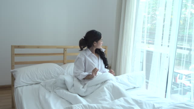 Asian Young Woman waking up on the bedroom video