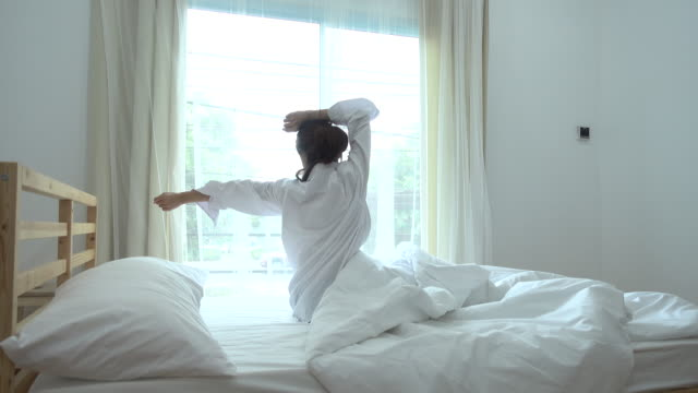 asian young woman waking up on the bedroom - ritemprarsi video stock e b–roll
