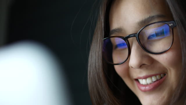 Asian Young Woman watching Information of computer screen, Reflection in glasses video