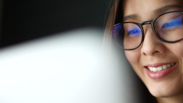 vídeos de stock, filmes e b-roll de asian young woman, observando as informações da tela do computador, reflexo em óculos - entusiástico