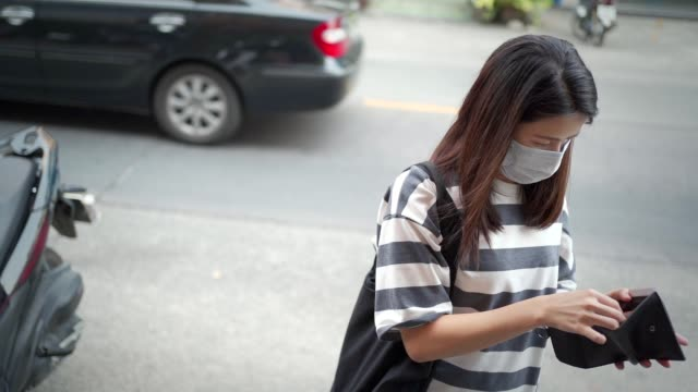 Asian young woman wear mask looking at wallet standing on the street side, covid-19 effect, new normal life 2020, world pandemic crisis, financial economic crisis, car pass by on back ground, slow mo outdoor shot, NEW NORMAL life concept, wear mask hot pockets stock videos & royalty-free footage