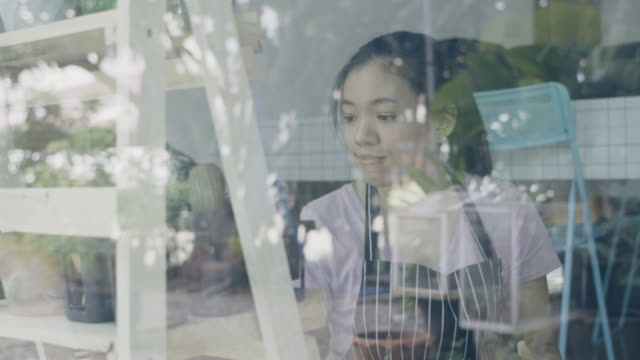 Asian young woman wearing apron caring for green indoor plant at home.New normal lifestyle concept of Hobby during quarantine and social distancing to stop spread disease of Coronavirus.4k Slow motion.