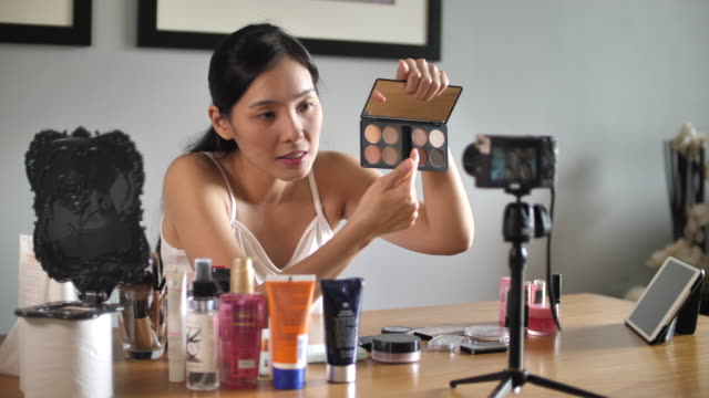 asian young woman youtube blogger recording vlog video with makeup cosmetic at home making online influencer on social media concept.live streaming viral - influencer filmów i materiałów b-roll
