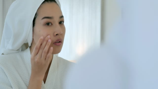 vídeos de stock e filmes b-roll de asian young woman's cheek with typical problem with acne and pimples in the adulthood time.young women with problem skin in bathroom.skin problem,acne,skin care concept - espelho