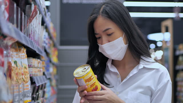 Asian young women age 25 yearold in protective medical mask buys basic necessities at supermarket during covid-19 coronavirus epidemic.Grocery Shopping concept.