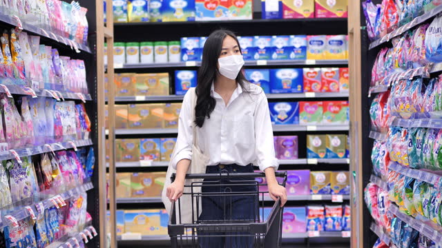 Asian young women age 25 yearold in protective medical mask buys basic necessities at supermarket during covid-19 coronavirus epidemic.She walks through empty supermarket or grocery store.Grocery Shopping conceopt.