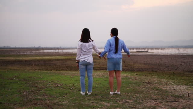 Asian Young women are having fun and laughing and walking and jump on the green field in the evening.
