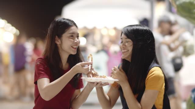 vídeos de stock e filmes b-roll de asian young women friends travel in bangkok, thailand, beautiful female feeling happy walking and eating pad thai at the khao san road. women travel eat street food concept. slow motion shot. - comida asiática