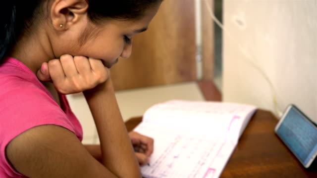 Asian/Indian girl doing online homework from home through smartphone and writing on a notebook.