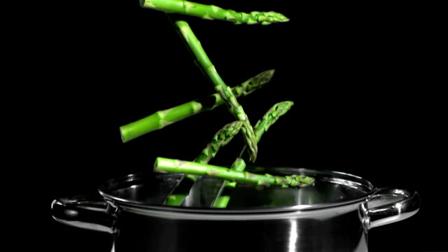 Asparagus falling in pot on black background video