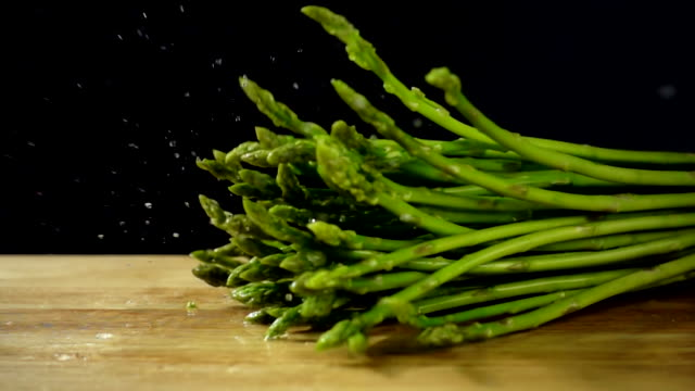 Asparagus stalks falling into cutting board in slow motion with water splashing