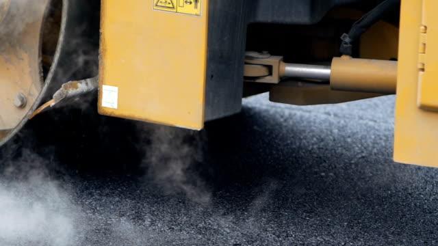 asphaltverlegung. straßenbau. eisbahn gerollter asphalt - asphalt stock-videos und b-roll-filmmaterial