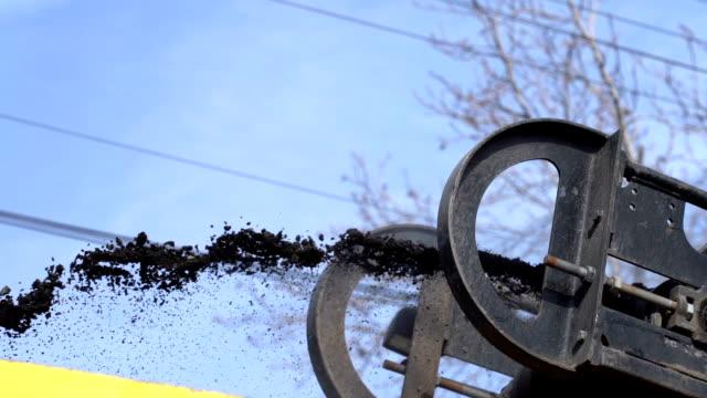 vídeos de stock e filmes b-roll de asphalt road milling machine unloading asphalt into the truck - slow motion - alfalto
