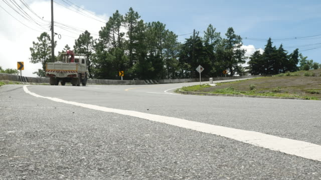 Asphalt road with the truck is driving up the hill.