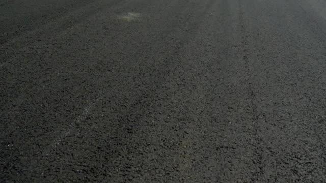 asphaltstraße mit weißen und farbigen streifen - asphalt stock-videos und b-roll-filmmaterial