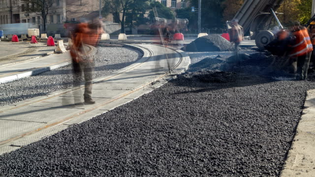 Asphalt roller and excavator on the road repair site during asphalting timelapse. Road construction equipment