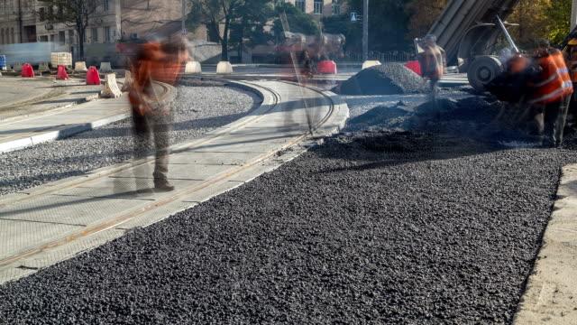asphalt-walze und bagger auf der straße reparieren website während der asphaltierung zeitraffer. straßenbauarbeiten - asphalt stock-videos und b-roll-filmmaterial