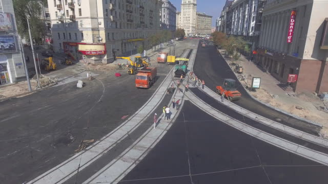 Asphalt spreading machine and vibration roller at pavement road works aerial