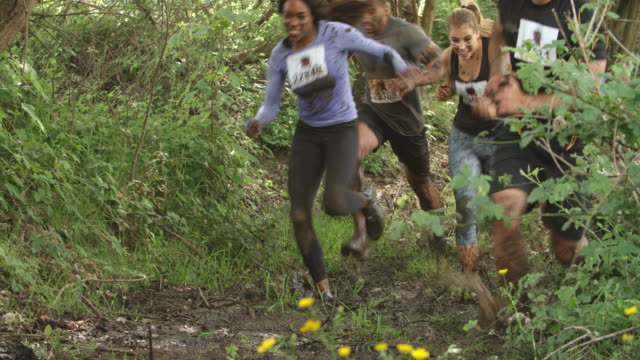 Assault course competitors running through forest, low angle video