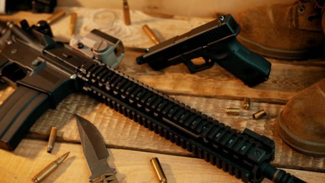 vidéos et rushes de fusil d'assaut et d'équipements militaires sur une table en bois - armement