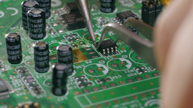 assembling a circuit board. soldering chip on motherboard - pinze attrezzo manuale video stock e b–roll