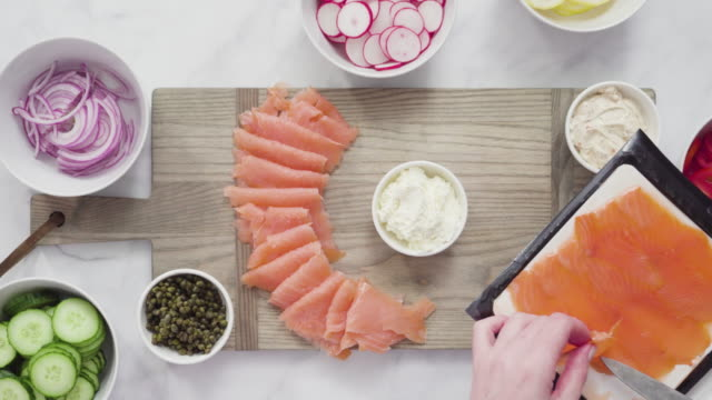 Assembling bagel brunch board with smoked salmon