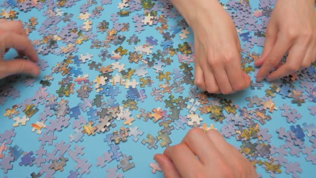 Assembling jigsaw puzzle. Hand matching jigsaw halves. Leisure activity. Achieving step by step Love concept. Engaging in successful work finding business solution, corporate unity