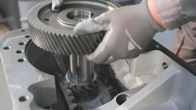 montaż skrzyń biegów w produkcji, mężczyźni montują motoreduktor. - dźwignia zmiany biegów filmów i materiałów b-roll