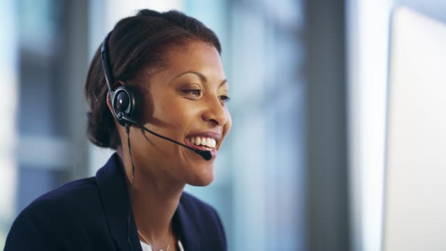 Assistance with a smile 4k video footage of an attractive young female callcenter agent working on a desktop in her office hands free device stock videos & royalty-free footage