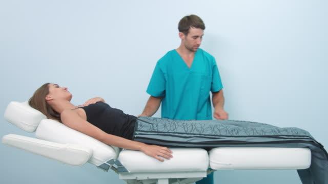 assistent hilft patienten nach kompressionstherapie - sauna und nassmassage stock-videos und b-roll-filmmaterial