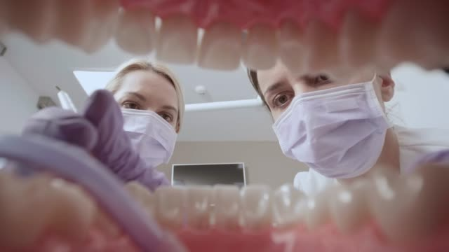 pov assistant placing a suction hose into the patient's mouth before dentist starts working on the tooth - dentist стоковые видео и кадры b-roll
