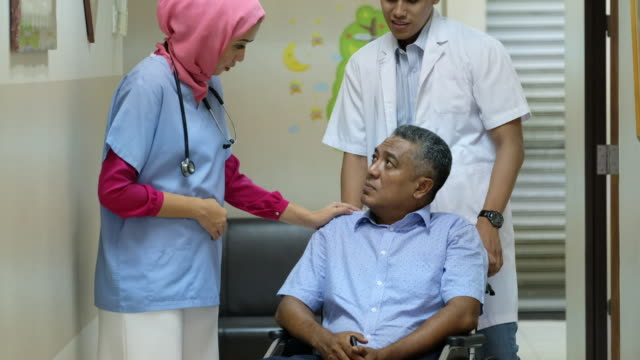 vidéos et rushes de aider le patient principal dans un fauteuil roulant - infirmière