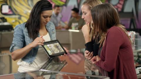 vídeos de stock e filmes b-roll de associate at a recreational marijuana shop using a tablet to show product to an older customer, close up - erva