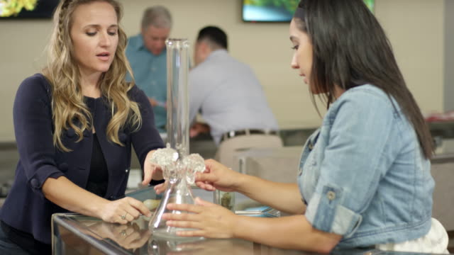Associate at marijuana shop showing an older customer how to use a bong video