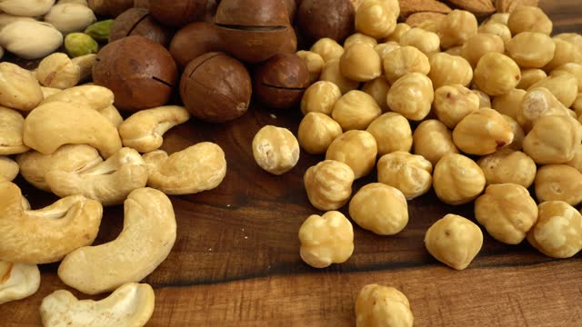 Assorted nuts on a wooden board. video