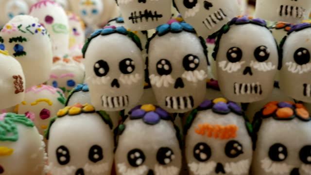 assortment of different sugar skulls for day of the dead -dolly - tradycja filmów i materiałów b-roll