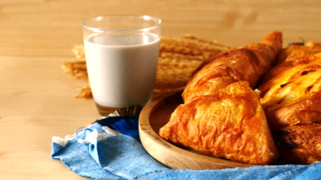 Assortment of pastries with milk on wooden table. Assortment of pastries with milk on wooden table background. pastry dough stock videos & royalty-free footage
