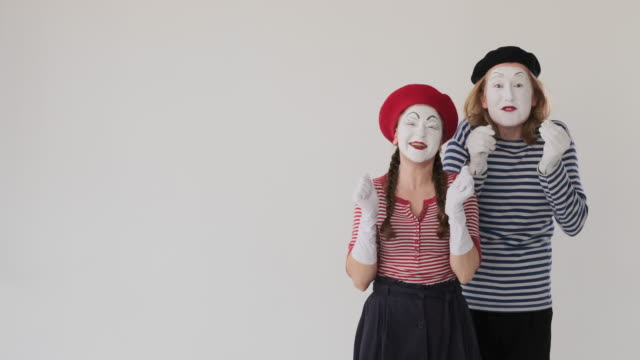 Astonished mime artists clapping hands