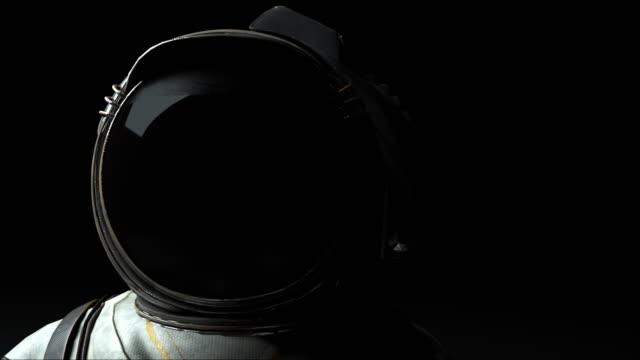 astronaut in einem metallhelm nah bei hell und dunkel. computergenerierter speicherplatzhintergrund, 3d-rendering - raumanzug stock-videos und b-roll-filmmaterial